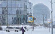 Прохожие идут по улице во время снегопада в Нур-Султане