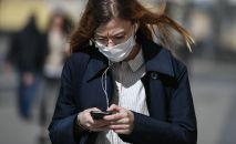 Девушка в защитной маске идет по улице со смартфоном в руках. Архивное фото