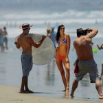 Девушка позирует фотографу на пляже Сан-Диего в Калифорнии, США