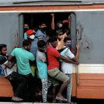 Пассажиры едут в переполненном поезде в Коломбо, Шри-Ланка