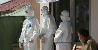 Медицинские работники у входа в дневной стационар. Архивное фото