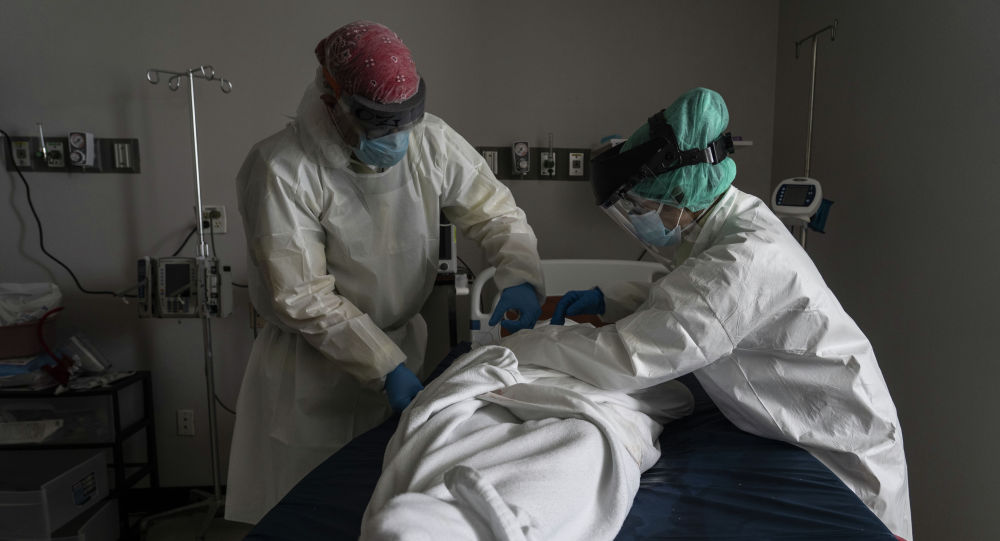 Медицинский персонал носит полный СИЗ, завернув умершего пациента простынями в отделении интенсивной терапии. Архивное фото
