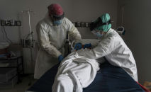 Медицинский персонал носит полный СИЗ, завернув умершего пациента простынями. Архивное фото