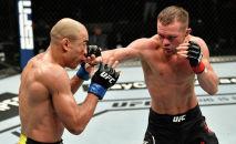 Петр Ян из России наносит удар по бразильскому бойцу Жозе Альдо в чемпионате UFC в легком весе во время соревнования UFC 251 на форуме Flash на острове Яс, Абу-Даби, Объединенные Арабские Эмираты. 12 июля 2020 года