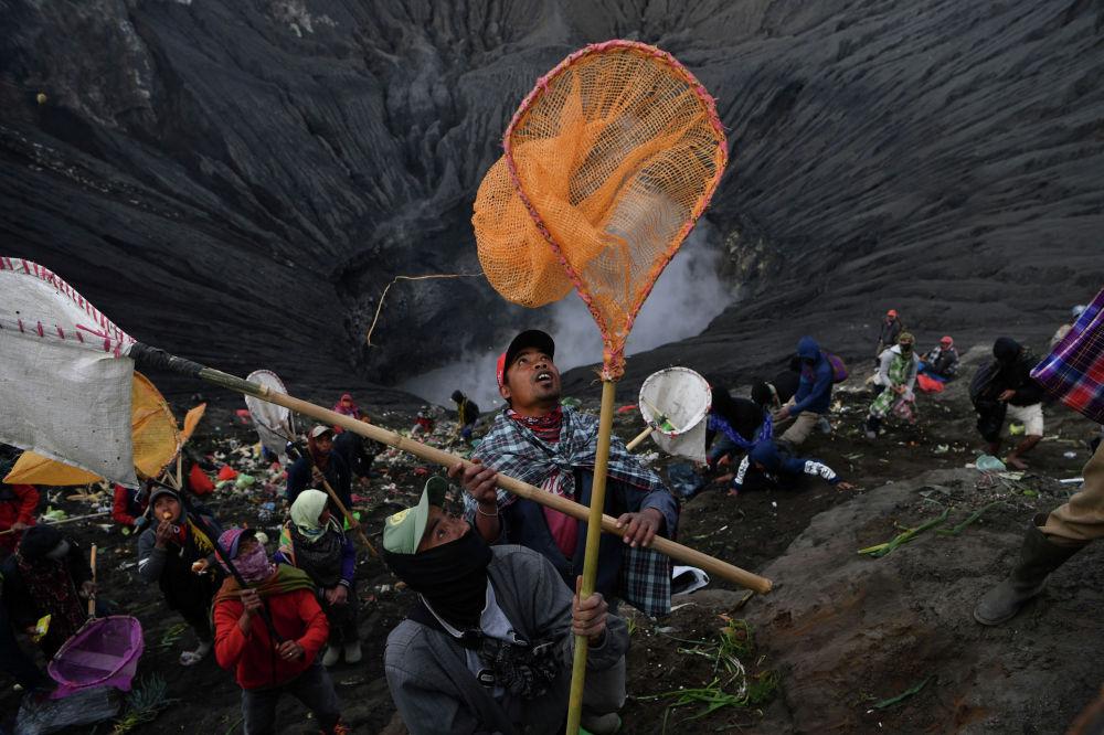 На традиционном фестивале Ядня Касада жители острова Ява ловят монеты и еду, приносимые в жертву вулкану Бромо.