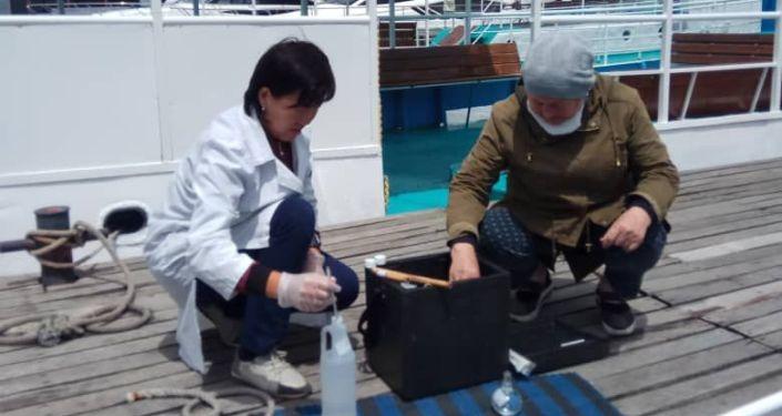 Изъятие пробы водыв озере Иссык-Куль сотрудниками Госагентства охраны окружающей среды и лесного хозяйства КР