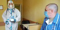 Врач проводит ежедневный обход-осмотр участника испытаний вакцины от коронавируса в Главном военном клиническом госпитале имени Н. Н. Бурденко в Москве.
