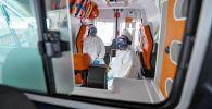 Медицинские работники в защитных костюмах на автомобиле скорой помощи. Архивное фото