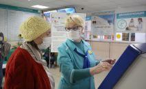 Сотрудница поликлиники помогает посетительнице получить талон к врачу. Архивное фото