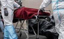 Медики в СИЗах перевозят умершего от COVID-19. Архивное фото