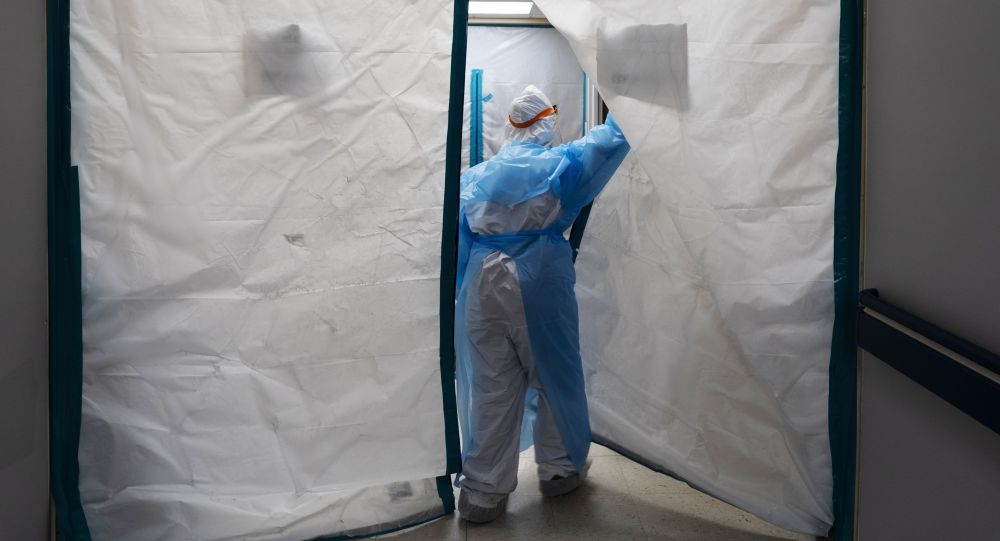 Медицинский работник в защитном костюме входит в красную зону в госпитале. Архивное фото
