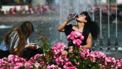 Девушки отдыхают у фонтана в жаркий день. Архивное фото