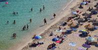 Люди загорают на пляже в Пальма-де-Майорка (Испания)