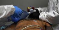 Медицинские работники лечат пациента с коронавирусной болезнью (COVID-19) в отделении интенсивной терапии коронавирусной болезни (COVID-19) Объединенного мемориального медицинского центра в Хьюстоне, штат Техас, США, 29 июня 2020 года.