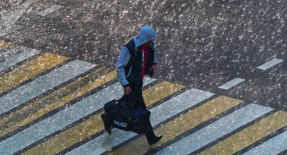 Человек переходит дорогу во время грозы. Архивное фото