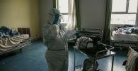 Медицинский работник в палате где проходят лечение пациенты с коронавирусом. Архивное фото