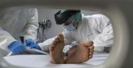 Медицинский персонал, закрывает тело мужчины умершего от коронавируса. Архивное фото