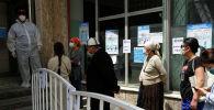 Люди стоят в очереди за пределами дневного стационара, открытого властями для лечения пациентов, инфицированных коронавирусной болезнью (COVID-19) в Бишкеке. Архивное фото