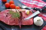 Мясо, перец, чеснок и помидор на разделочной доске. Иллюстративное фото