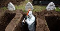Работник в защитном костюме роет могилы предполагаемым жертвам COVID-19