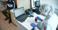 Аэропортто жүргүнчүдөн анализ алып жаткан медицина кызматкери. Архив