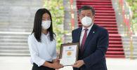 Жалпы республикалык тестирлөөдөн эң жогорку балл алган Акмарал Нурбек кызы Алтын сертификатты алуу учурунда