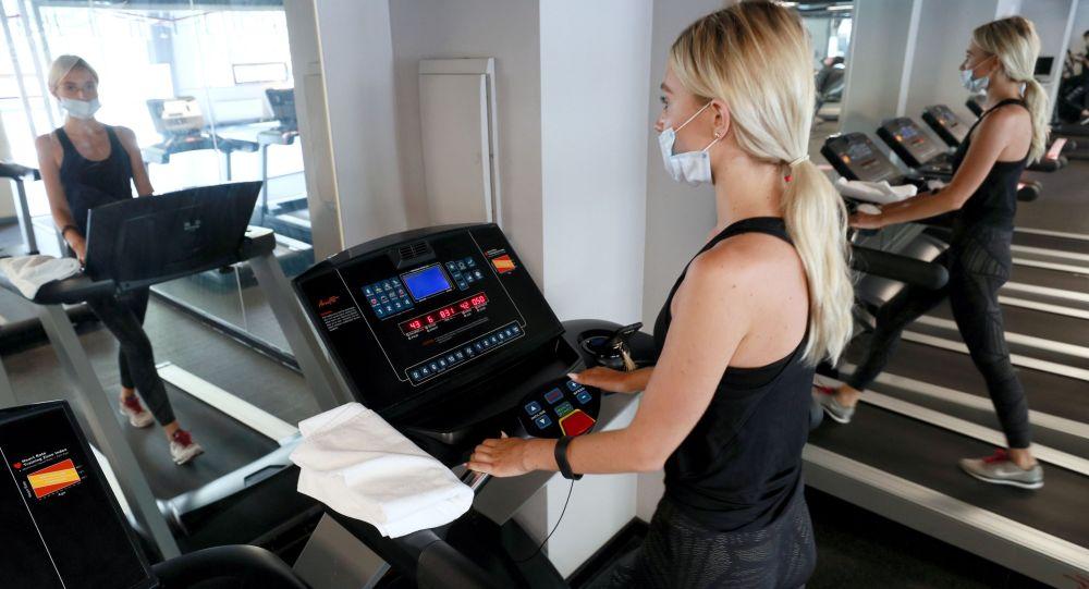 Девушка в медицинской маске на беговой дорожке в фитнес-клубе. Архивное фото