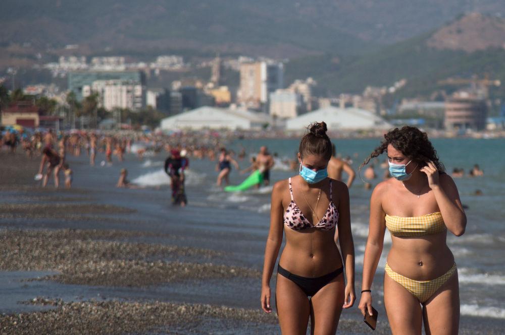 Девушки в защитных масках на пляже Мизерикордия в Малаге, Испания