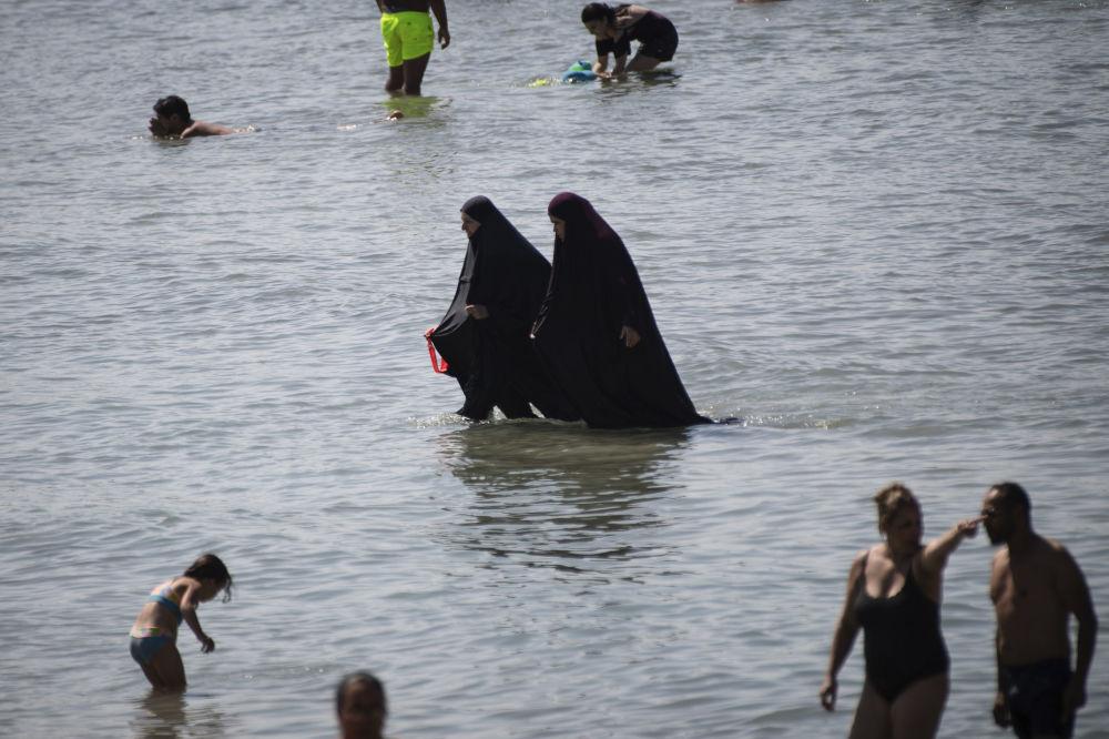 Мусульманки в чадре купаются в море на пляже в Марселе, Франция