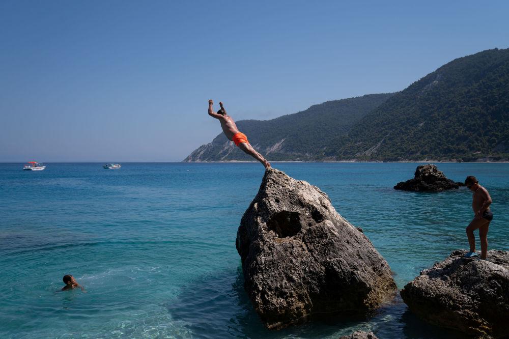 Мужчина ныряет на пляже Агиос Никитас после смягчения мер по борьбе с распространением коронавируса на острове Лефкас, Греция