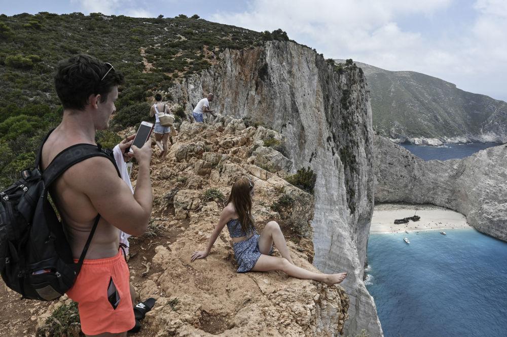 Туристы на скалах у пляжа Навайо, Греция