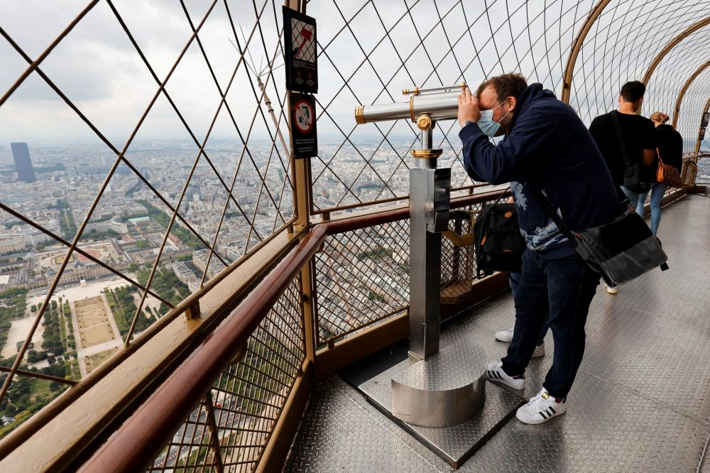 Мужчина у монокуляра на смотровой площадке на Эйфелевой башне, Париж