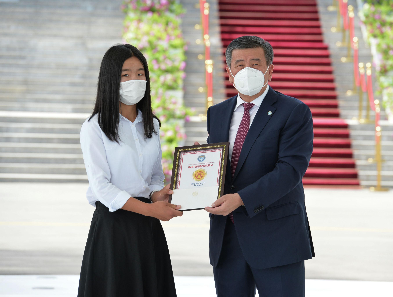 Президент КР Сооронбай Жээнбеков во время вручения Золотого сертификата набравшей самый высокий балл на Общереспубликанском тестировании (ОРТ) Акмарал Нурбек кызы