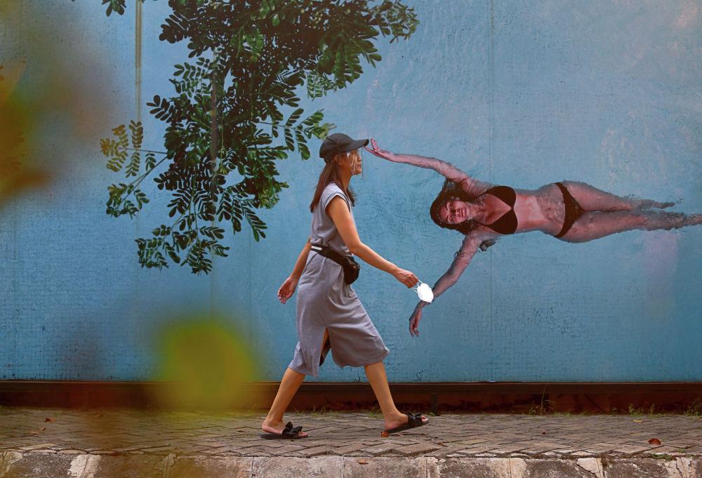 Женщина в защитной маске идет по улице Джакарты.