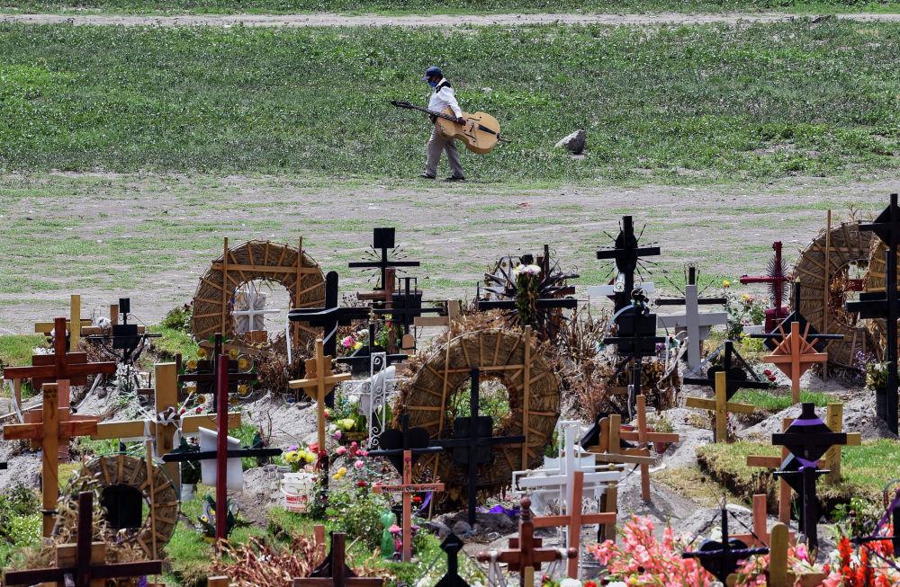 Родственник умершего от COVID-19 идет по кладбищу в штате Мехико. Всего в Мексике от коронавируса умерли более 47 тыс. человек