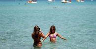 Женщины на пляже Монделло в Палермо.