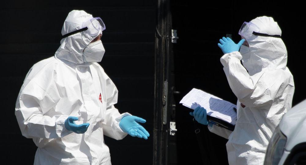 Медицинские работники в защитном снаряжении во время разговора