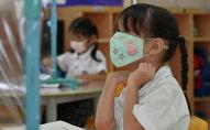 Школьница играется с маской во время урока. Архивное фото