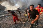 Пожарные выносят пострадавшего с места взрыва в Бейруте