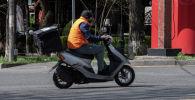 Мужчина едет на скутере. Архивное фото