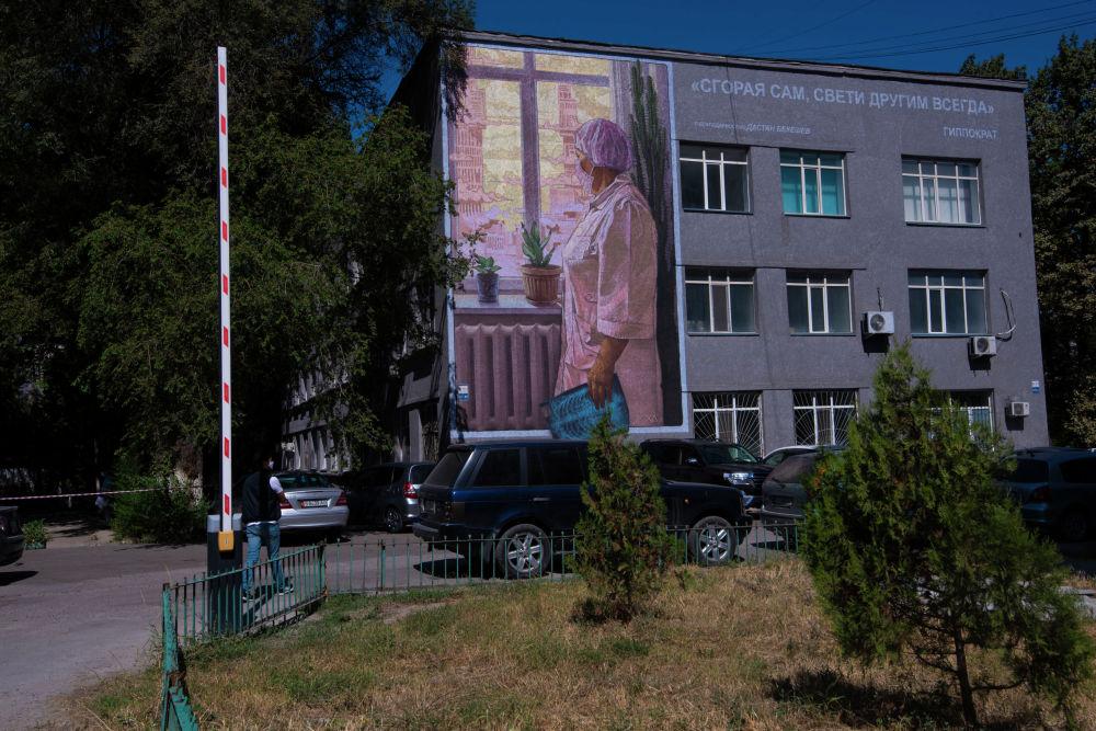 Граффити Сгорая сам, свети другим всегда группы художников Doxa на стене одного из корпусов Национального госпиталя в Бишкеке
