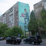 Граффити Мальчик с лейкой группы художников Doxa на стене жилого дома в Бишкеке