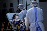 Медицинские работники перевозят пациента с подозрением на заражение COVID-19