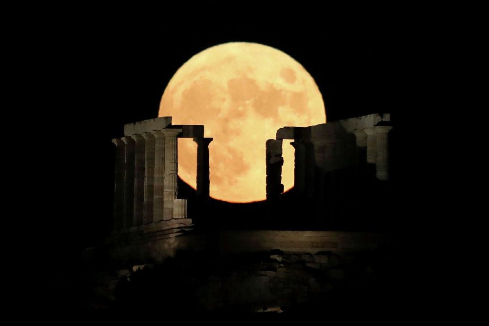 Полная луна восходит за храмом Посейдона на мысе Сунион, недалеко от Афин, Греция, 3 августа 2020 года