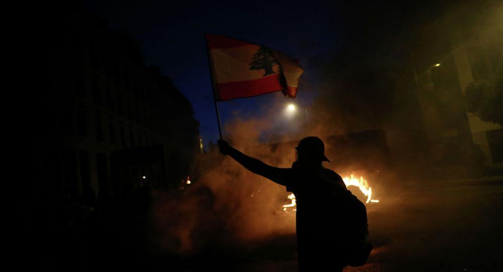 Демонстрант держит флаг Ливана во время акции протеста после взрыва во вторник в Бейруте, Ливан, 8 августа 2020