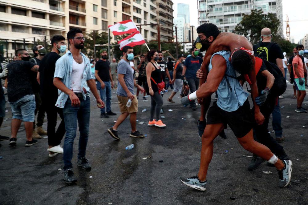 Раненый демонстрант эвакуируется во время акции протеста после взрыва во вторник в Бейруте, Ливан, 8 августа 2020 г