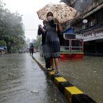 Люди на затопленной ливневыми дождями улице в Мумбаи, Индия. 4 августа 2020 года