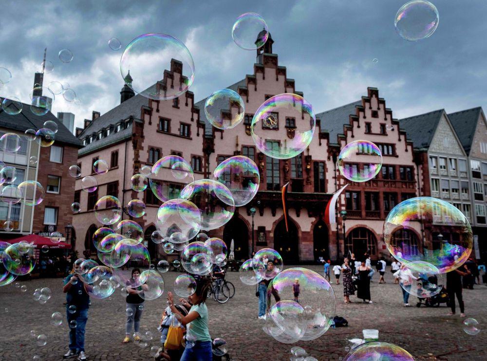 Уличный артист пускает мыльные пузыри перед зданием ратуши во Франкфурте, Германия. 3 августа 2020 года