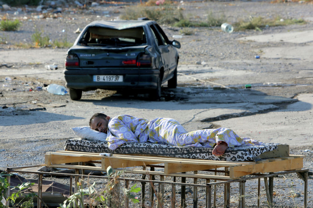 Мужчина спит около своего дома в Бейруте, уничтоженного после сильного взрыва в порту, Ливан. 6 августа 2020 года