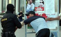 Офицеры ОМОНа задерживают мужчину во время митинга оппозиции